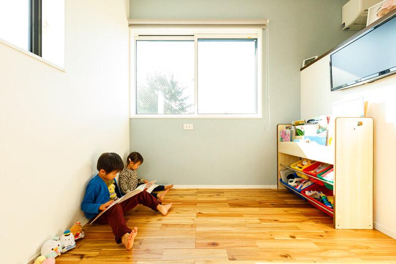 ライトグリーンのアクセントクロスを使った2階の居室。絵本やおもちゃを自分たちで整理できるようにマガジンラックを置いて、子どもたちの空間にしました。右手の壁の向こうは書斎スペース。閉じた空間にしないことで、互いの気配が伝わります。