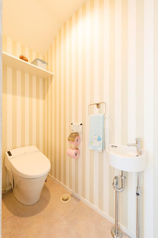 清潔感のあるかわいいストライプのクロスを採用したトイレスペース。シンプルで美しく、また楽しく居心地のいい空間にすることで、子どもたちのトイレトレーニングも捗ります。