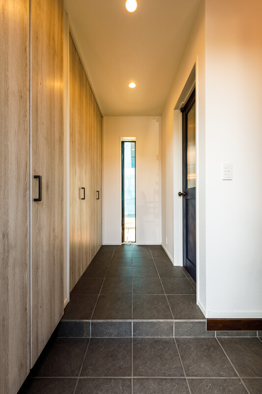 奥行きの深い土間フロアの玄関は、クラシカルなドアのしつらいも相まってモダンアメリカンな世界観のある空間に。一面にクローゼットが並び、収納量も十分。縦長のスリット窓の向こうには、テラス越しに内庭が見えます。右手は、家族のシューズクロークになっています。