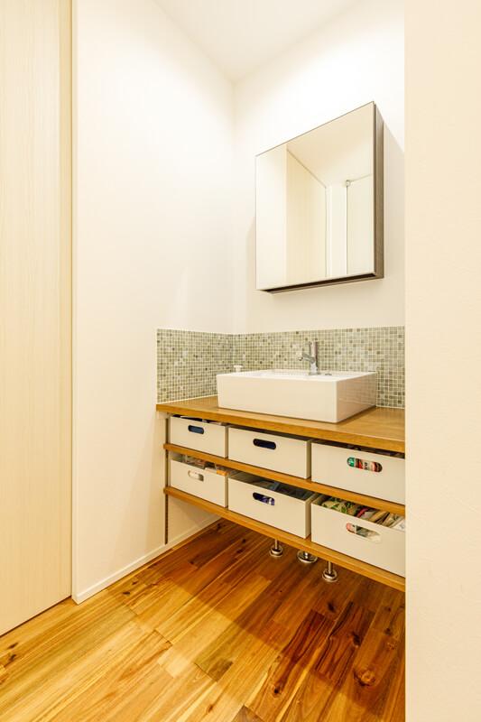 キッチンの脇に洗面洗濯スペース、浴室をレイアウトしました。水回りを集中させて家事動線を短くして家事の負担を減らしています。洗面台は、形の美しいスクエアの鏡と目の細かいモザイクタイルを組み合わせたモダンデザインに仕上げています。