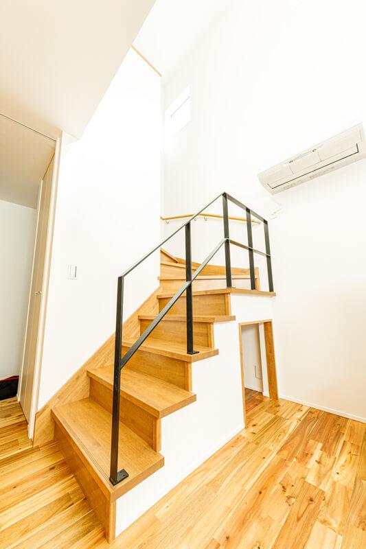 吹き抜けの階段は開放感を損なわないように、手摺りをスチールのスケルトンとしました。階段下のスペースを活かした大容量のリビング収納のおかげで、置き家具をなくして生活空間はすっきり。