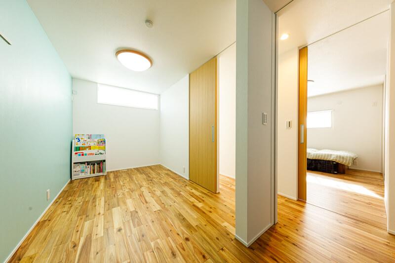 2階は家族のプライベートスペース。壁に淡いグリーンのアクセントクロスを敷いたフリースペースは、子ども部屋。仕切り壁を入れて、2つの部屋にセパレートすることもできます。