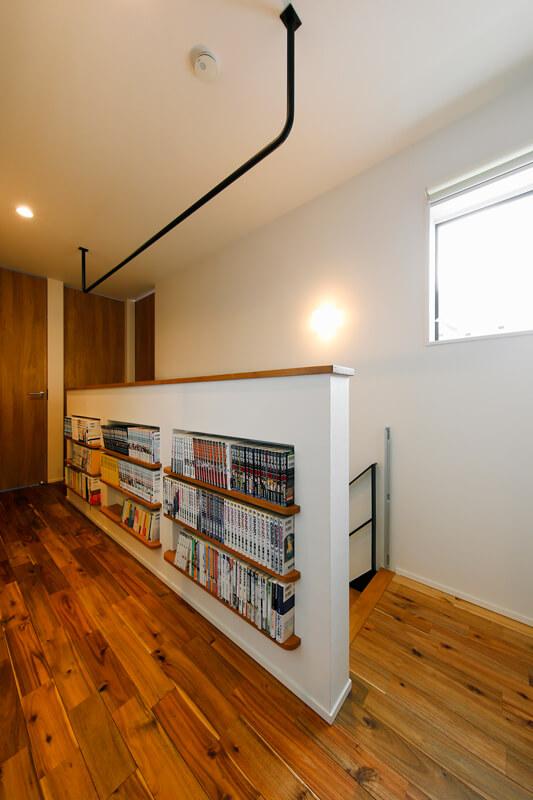 階段室の腰壁は、本棚とディスプレイを兼ねたニッチ収納としての機能性を持たせました。陽だまりが心地よく、廊下に座り込んでくつろいで過ごせるファミリーライブラリーです。天井にハンガーパイプを取り付けていて、サンルームにもなります。