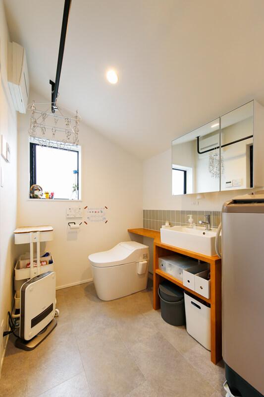 コンパクトで機能性にあふれた洗面室は、天井の勾配を活かしてハンガーパイプを配置しています。洗面台回りには木のカウンターを造作して、タイルを組み合わせて清潔感のある仕上がりに。