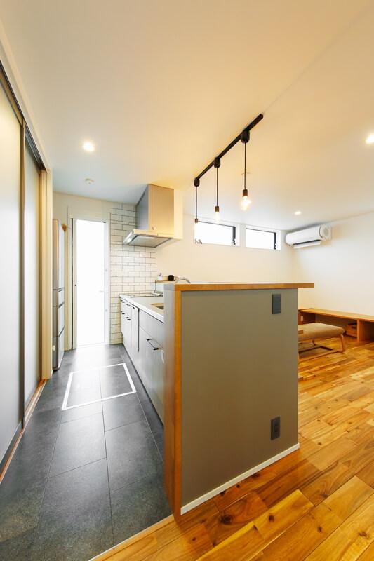 勝手口のテラスドアからも光が満ちる明るいキッチン。毎日使うからこそ、キッチン床は汚れが目立ちにくいストーン調のクロスにしました。玄関やリビング側から手元が見えないようにカウンターを高く立ち上げています。奥の壁はホワイトタイル貼りに。