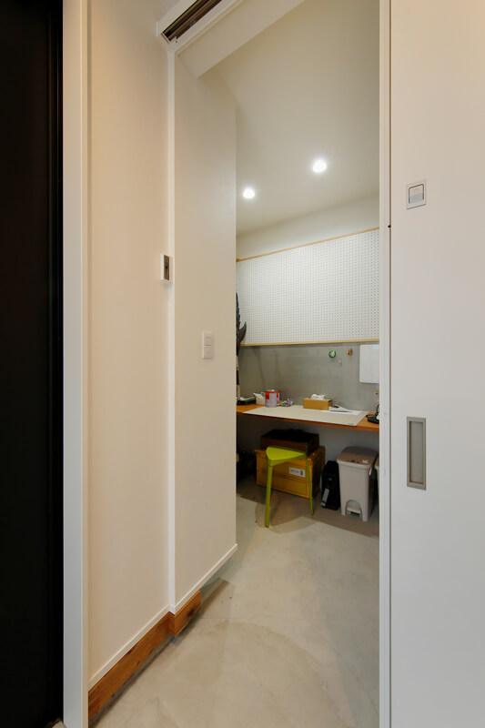 広々とした土間玄関の一角にはご夫婦の作業部屋を作りました。知らないうちに子どもが入って怪我したりしないように、鍵は高い位置に付けてあります。カウンター正面の壁はパンチングボードにして、自由に棚やフックを取り付けられるようにしています。