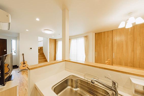 オープンキッチンに立つと、LD全体はもちろん、玄関、階段まで見渡すことができます。右に見えるのが衣類も収まる大型収納です。