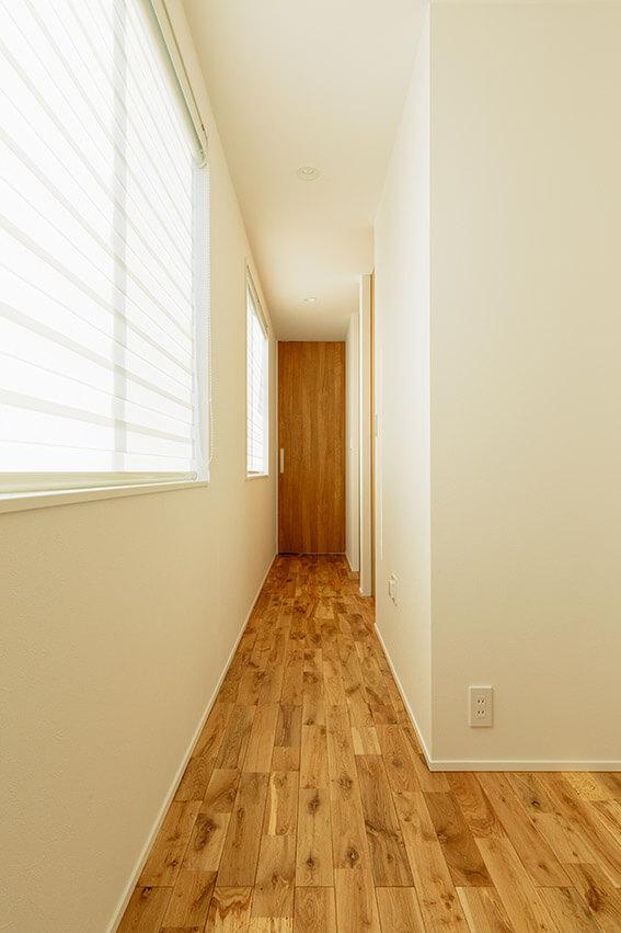 階段を上がったところに続く2階の廊下。大きな開口部を設けているので、開放感がある。2階にはプライベートな個室を3室設置しました。一番手前が子ども部屋に。奥が寝室となっています。