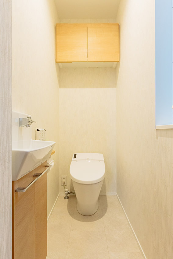 コンパクトな空間ながら、十分な収納を備えたトイレ。省スペース設計の手洗いコーナーも設置しました。