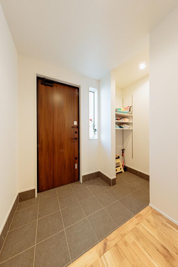 充分な広さを備えた玄関。収納部分にはあえて建具等を設けず、靴をはじめフレキシブルに利用できるように設計しました。