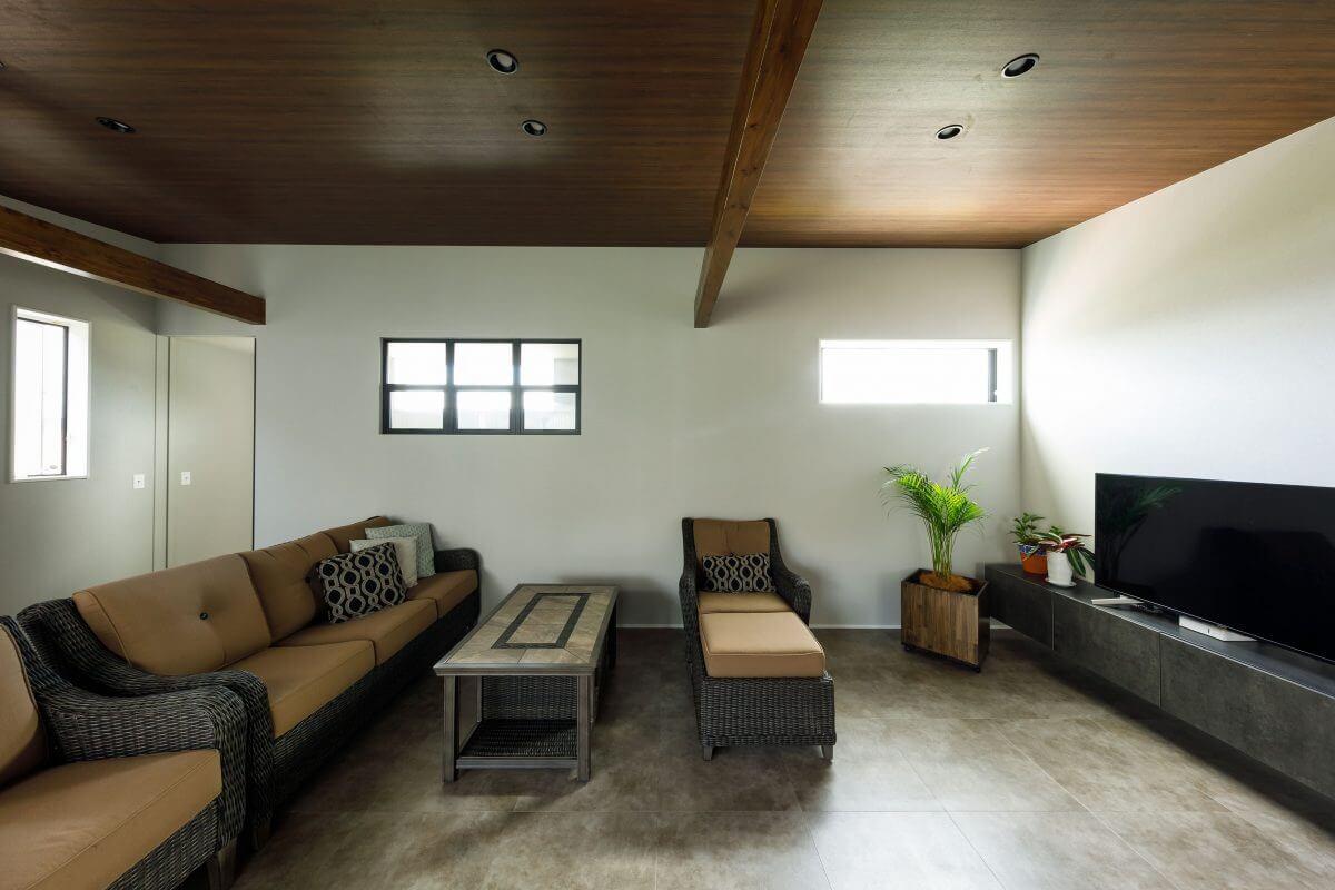大きなもので、横幅3m近くあるゆったりとしたソファーが違和感なく溶け込む子世帯の2階LDK。正面に見える格子窓の向こうは階段室になっていて、こぼれる光がしっとりとしたリゾート感を演出します。