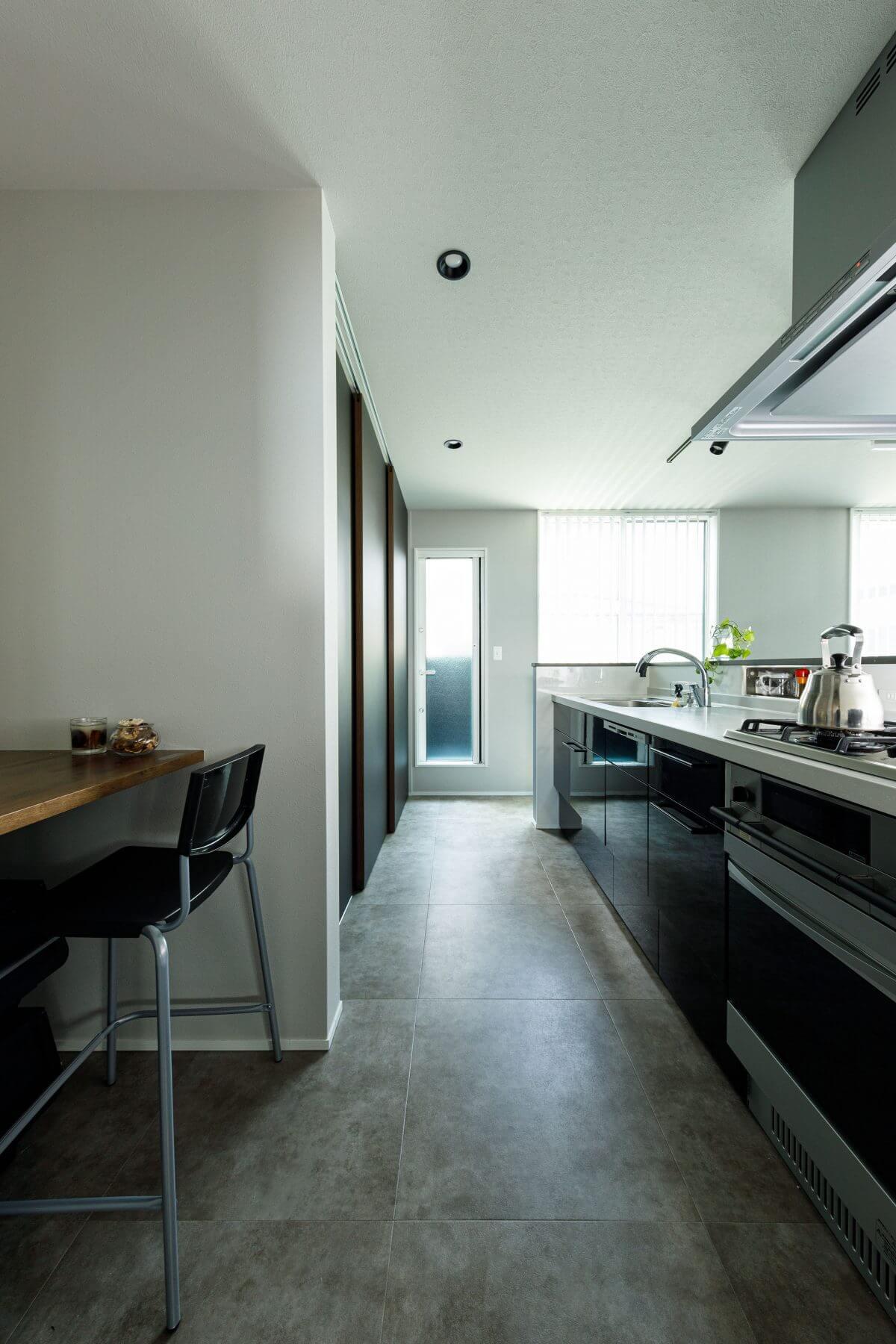 2階子世帯のキッチンはセミセパレートの対面型。手前左に見える少し明かりを抑えた落ち着く空間には多目的カウンターを設置しました。レシピを調べたり、家事の合間に休憩したりと何かと便利な場所。家事ラクを考慮した便利な提案が随所にみられる住まいです。