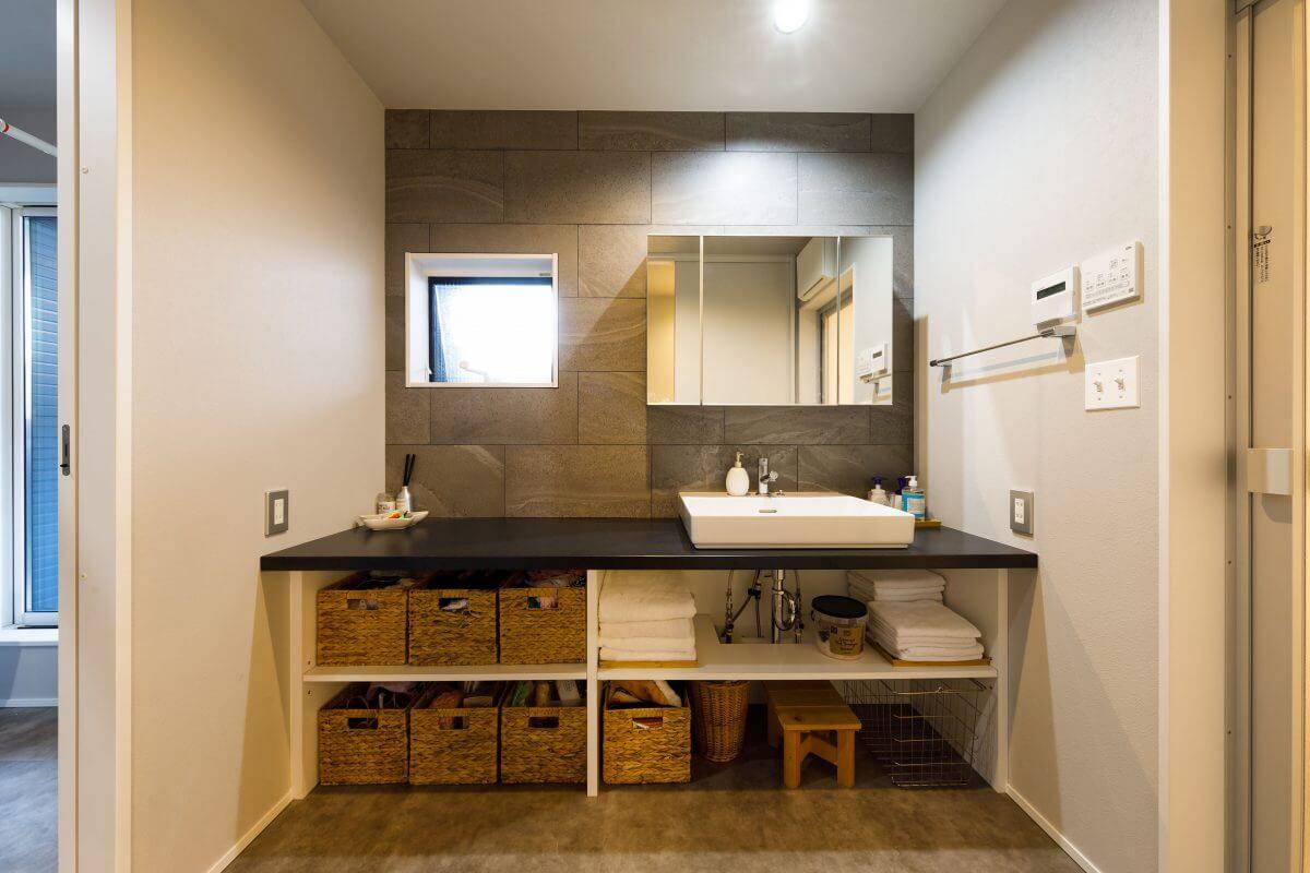 子世帯の洗面室はまるでリゾートホテルの洗面スペースのようなデザイン。機能的なオープンシェルフは、籐製のバスケットがきれいに3つ収まるように造作するなど、施主の暮らしのイメージを大切に細部を設計。左側が洗濯コーナーで右側が浴室へ。「家事動線が一直線につながり、動きやすい!」とNさん。