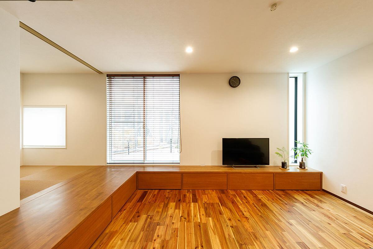小上がりの段差を利用して、テレビ台まで一体となる収納スペースとして造作しました。テレビ台部分は、ベンチとしても使用できるなど、多目的な使い方ができます。床のアカシアの無垢材とも、色味をコーディネートしています。