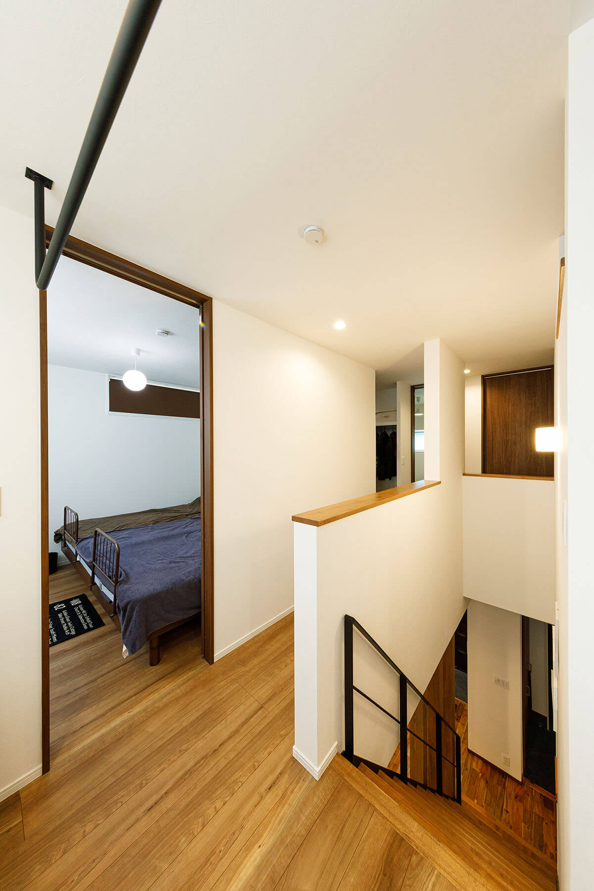 階段のすぐ脇が寝室になっています。階段の先は玄関なので、夜仕事から帰宅後は、そのまま2階まで上がり、写真の右側にある水まわりコーナーで手洗いや入浴を行い、左の寝室へ行き就寝することができます。