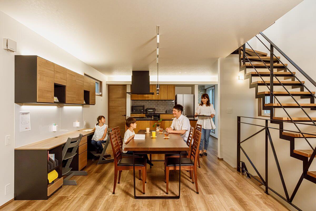 2階のダイニングは家族の団らんに特化したシンプル空間。ご夫妻とお子さんの距離が近くて、のびのびと過ごされています。適量適所の収納計画で居室はいつもスッキリ。木の質感と、右に見える黒のアイアン素材が調和しています。ちなみに、アイアンの柵(手すり)は、コジマジックさんの頭文字「K・M」になるようにデザインしました 。