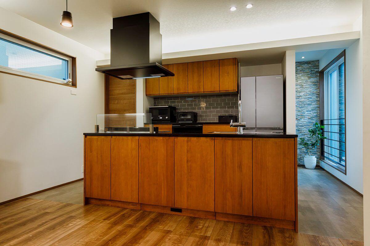 ご夫妻でアイデアを出し合ったキッチンはアイランドスタイルで、背面には壁面収納、さらにその奥には収納力抜群のパントリーが隠されています。「ぐるっと回れるラウンド式で、使い勝手がいい」と奥様はご満悦