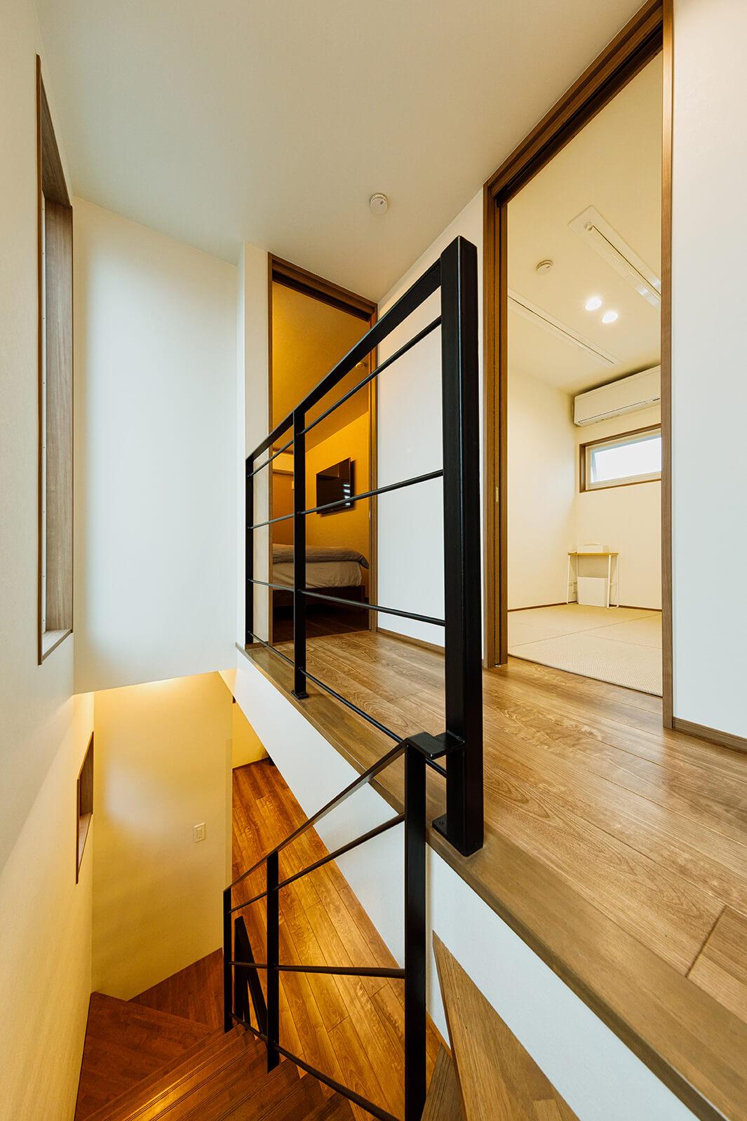 2階から階段を上がると3階の部屋がオープンにつながっています。採光を配慮してスケルトン階段を採用。左手奥が主寝室。
