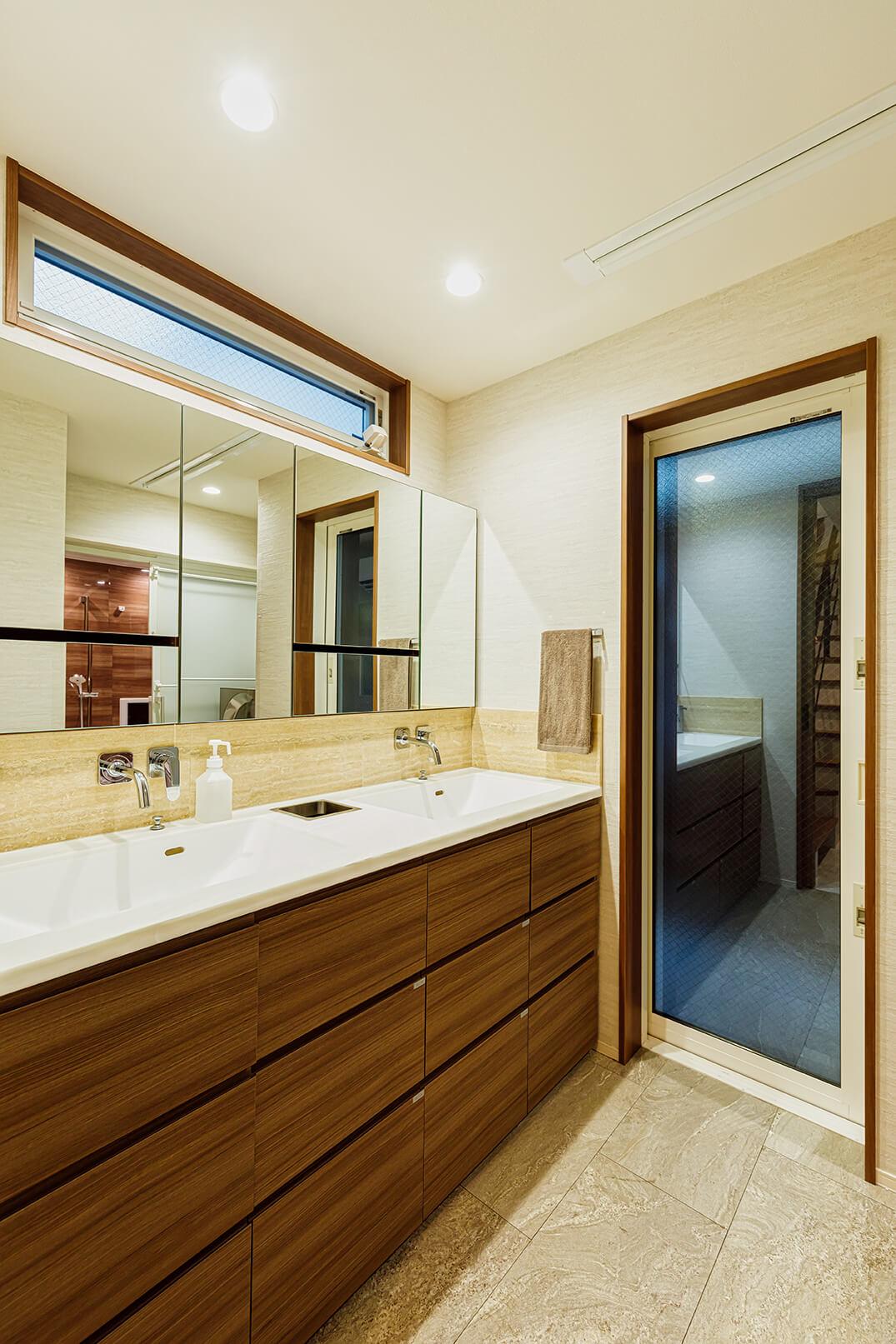 洗面室はタイルと木の温もりを活かした清潔感あふれる設計。2つの洗面ボウルが忙しい朝には重宝します。このスッキリとした空間を実現しているのが隠された収納。「主人はいちばん時間をかけて計画していました」と奥様