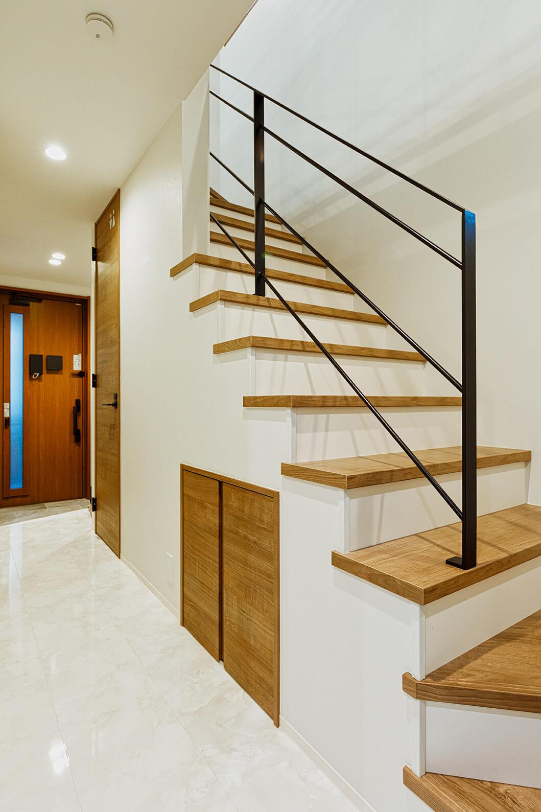 1階の玄関ホールと廊下・階段室。大理石の質感を感じさせる床が映えます。階段には天井までのドアが目を引くトイレと階段下収納を配置。左手にシューズクローク、書斎、ファミリークロゼットがあります。