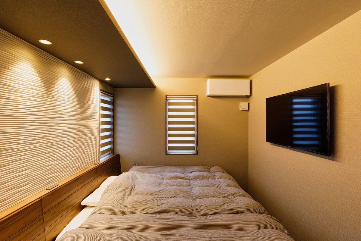 3階の南側に配置された主寝室。間接照明や表情のある壁面など、リラックス効果の高い演出が施されています。ベッドのヘッドボードを壁と一体化させ、スマホ充電用の差込口を設けるなど細かな工夫も見どころです。