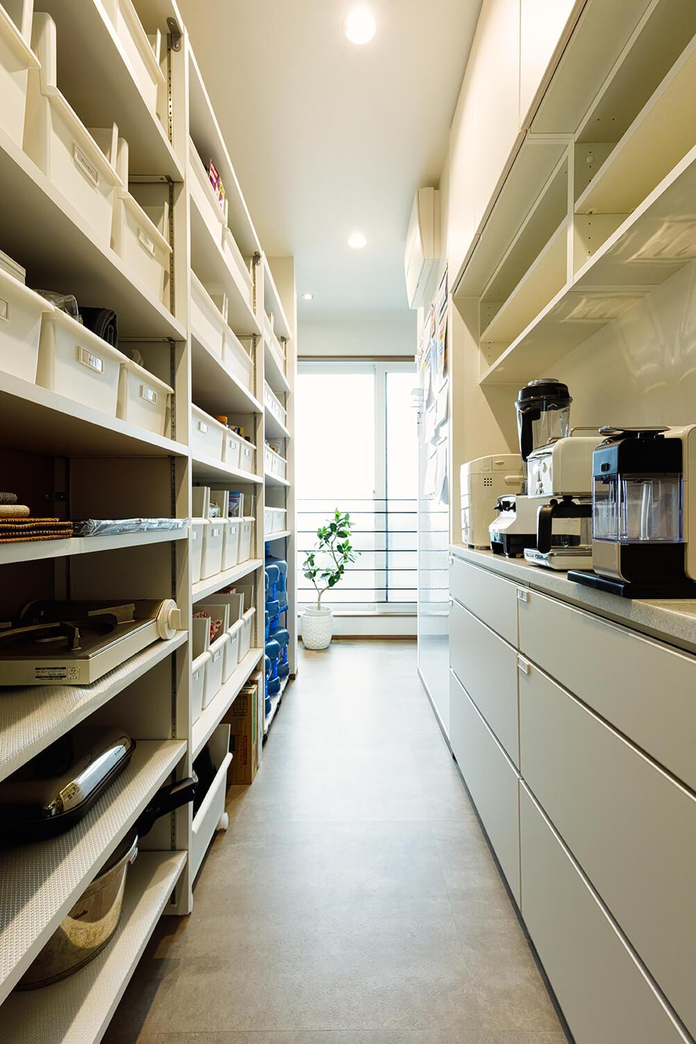 キッチン背面に設けた3.3畳のパントリーはぜひとも参考にしたい収納の1つです。キッチンの両サイドからアクセスできるのも好評。棚に入れた白い収納ボックスも見どころ。通路は幅750㎜とゆったりとしたサイズです。