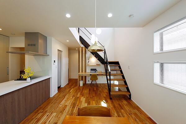 階段下を利用したスタディカウンターのある1階メインスペース。左のキッチンとダイニングスペースは玄関から間仕切りなくつながり、グルグルと回遊できる間取りに。左に見える出入り口の向こうが玄関になっています。