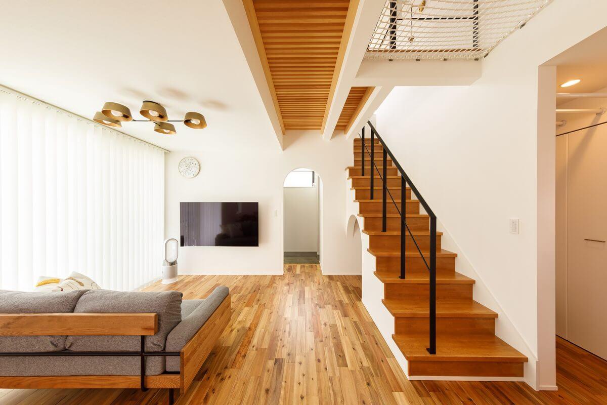 キッチンからリビング全体を見た様子。2階の廊下をスノコ張りにして、上階の光が階下に落ちるように設計しました。敷地は旗竿地にあるため、将来的に左側の開口部分が多少日陰になっても、室内に明るい光が降り注ぐように考えられています。
