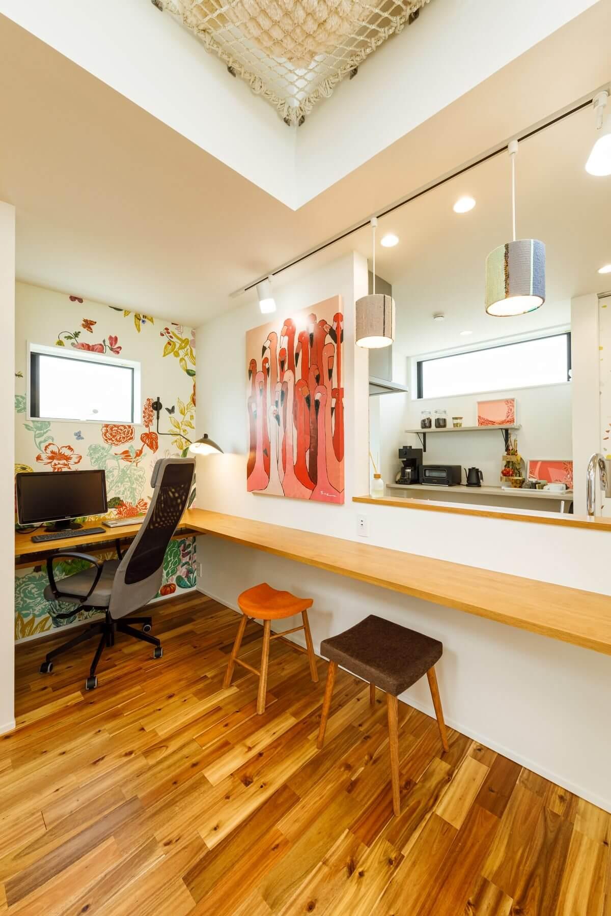 キッチン前のL字カウンター。カラフルなテキスタイルが描かれた壁紙の採用や、アートを飾り、個性が光る空間に。L字の短辺部分のカウンターはご主人の書斎コーナーになっています。仕事はもちろん、簡単な食事もできる多目的な空間です。