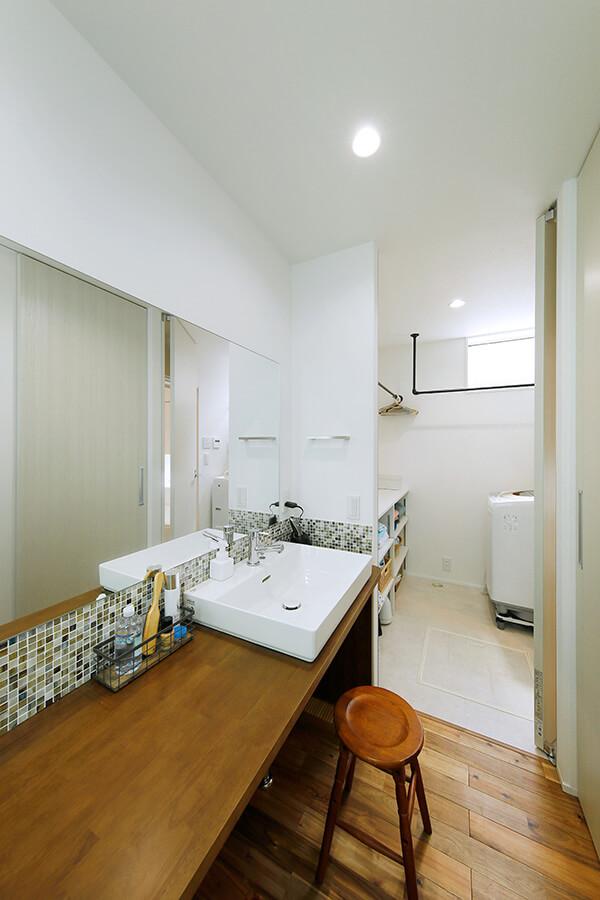 お気に入りのモザイクタイルで演出した洗面室。奥の脱衣室とつながり、全体としてランドリースペースとして機能します。