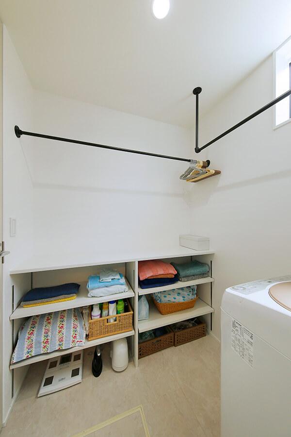 洗面室とつながる脱衣室。腰高サイズの造作棚は、洗濯物をたたんだり、アイロンがけをするのに最適な場所。この脱衣室と洗面室には、随所に室内干し用の物干しバーを設置しています