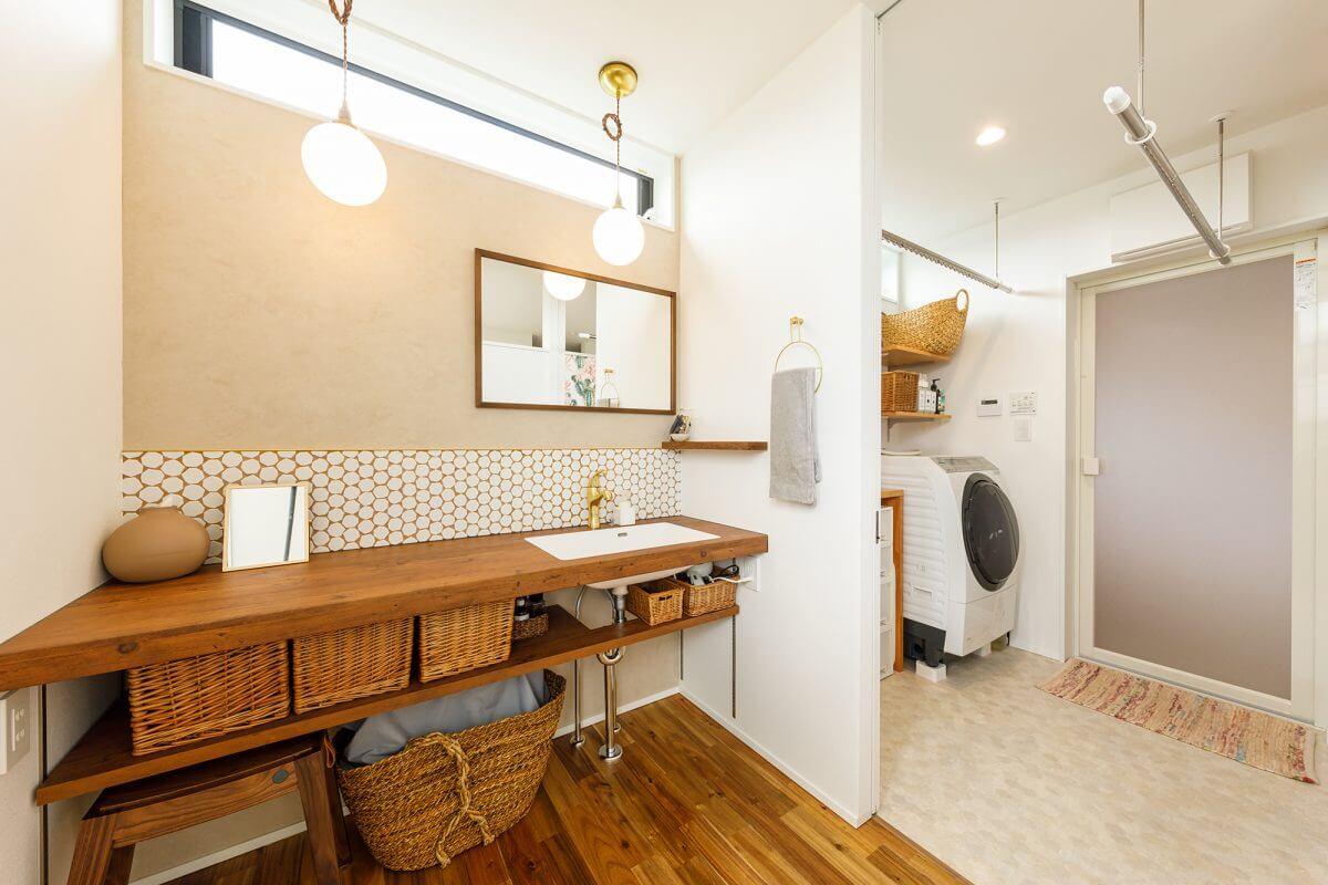 2階に上がった先にすぐ見える洗面コーナー、脱衣スペース、浴室へとつながる動線。全体が室内干しコーナーにもなっている機能的な場所です。造作の洗面コーナーに貼ったハニカム柄のタイルは奥様のお気に入りです。