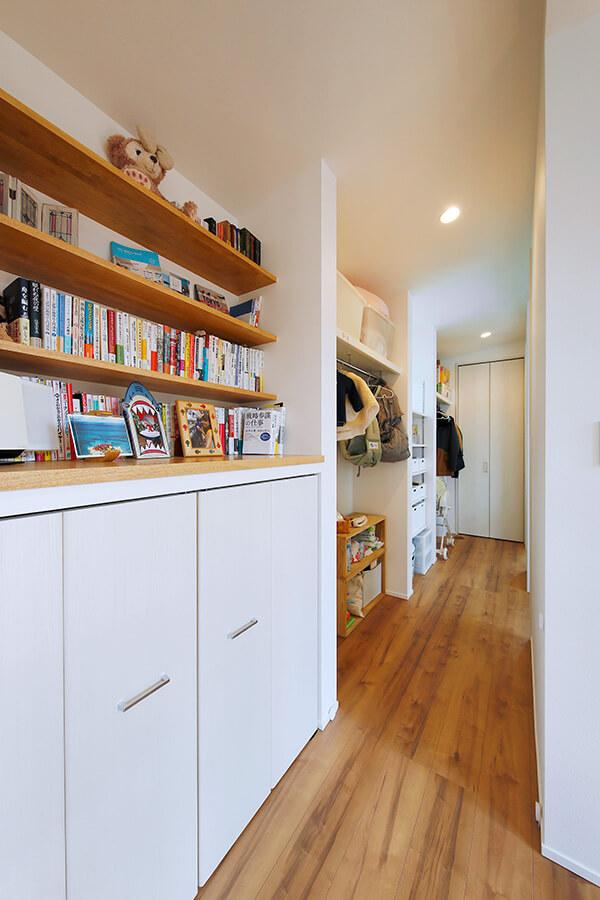 奥の子ども部屋につながる2階の廊下。廊下の脇に本棚や収納棚、子どものオープンクローゼットを設置することで、「通路と収納」を兼ねる設計に。限られたスペースを有効に活用しています。