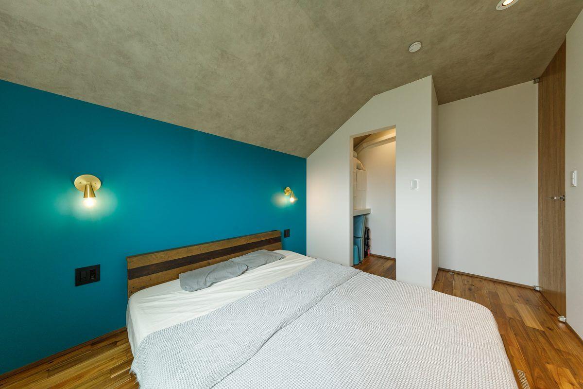 壁紙にこだわったり、リゾートライクな空間を演出した主寝室。ミニマムサイズのクローゼットに布団を収納できるなど、何かと機能的。斜線規制による勾配天井が、おもしろいフォルムの空間をつくっています。