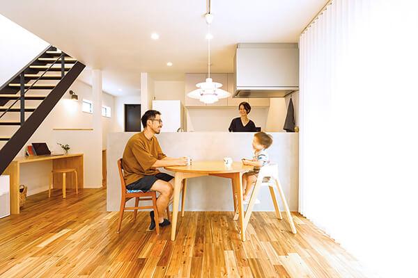 お気に入りのモルタル仕上げのオープンキッチンを中心に、一家で団らんを楽しむKさんご家族。左側に見える階段下の多目的カウンターは、夫人のテレワークスペースとして活用。