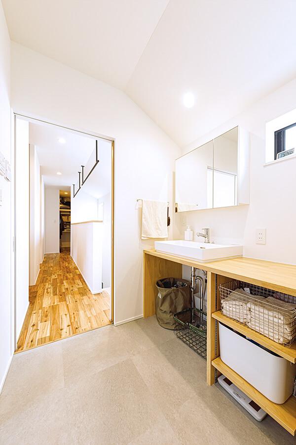 2階の造作の洗面コーナー兼洗濯室。奥の廊下は物干しコーナーも兼ねており、洗濯後に室内干しをする時に最短でつながるように設計されています。