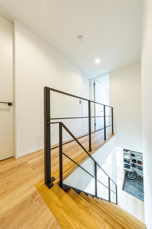階段吹き抜けを通じて、玄関にも明るい光を届けています。アイアン製の階段から続く2階廊下の手すりも、アイアン製でトータルコーディネート。