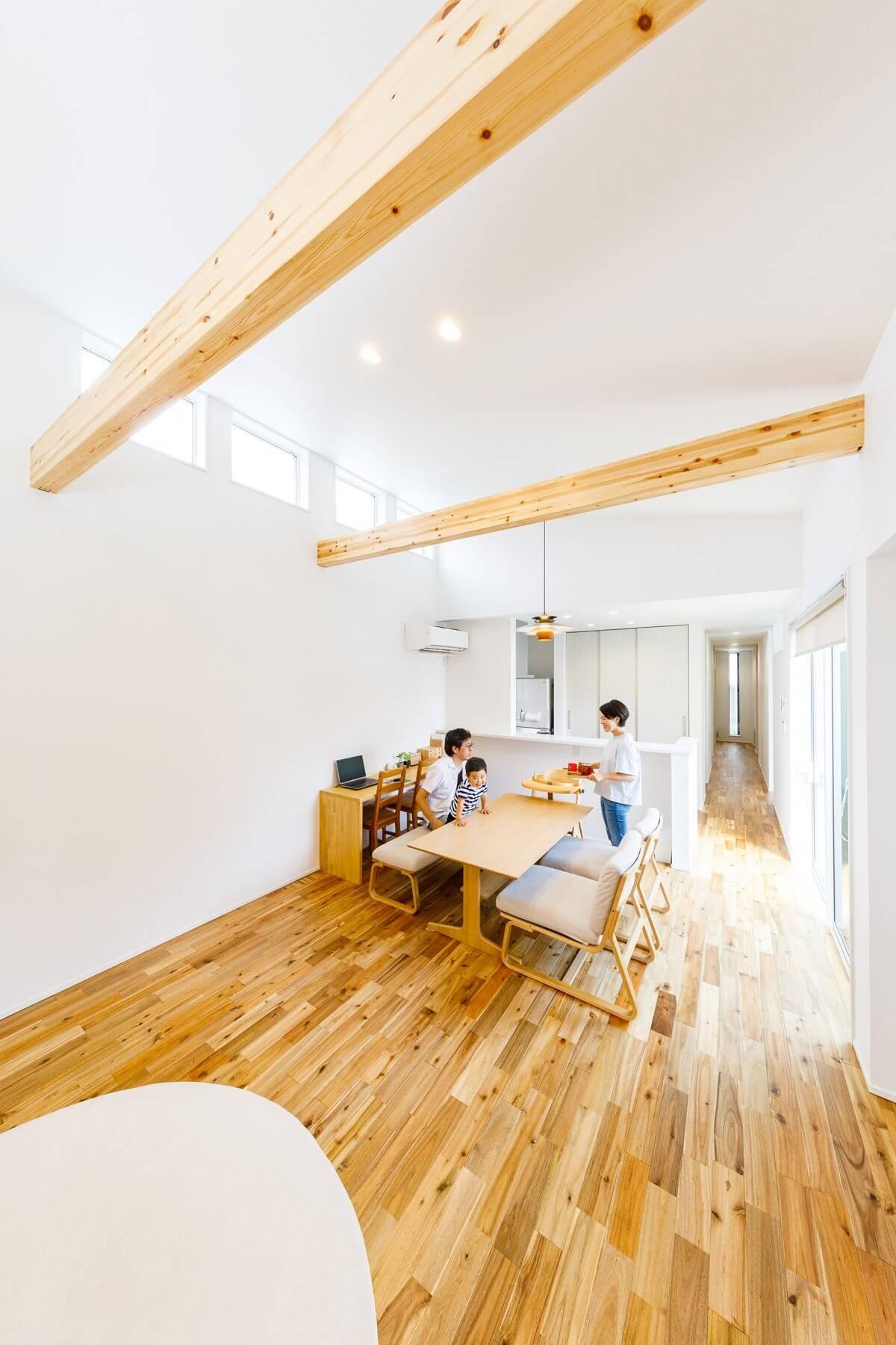 勾配天井を生かした吹き抜けが開放感を演出するLDK。天井の梁をダイナミックに見せることで、木のぬくもりをプラス。お隣の住宅からの視線が気にならないように、ハイサイド窓から光を採る設計としました。