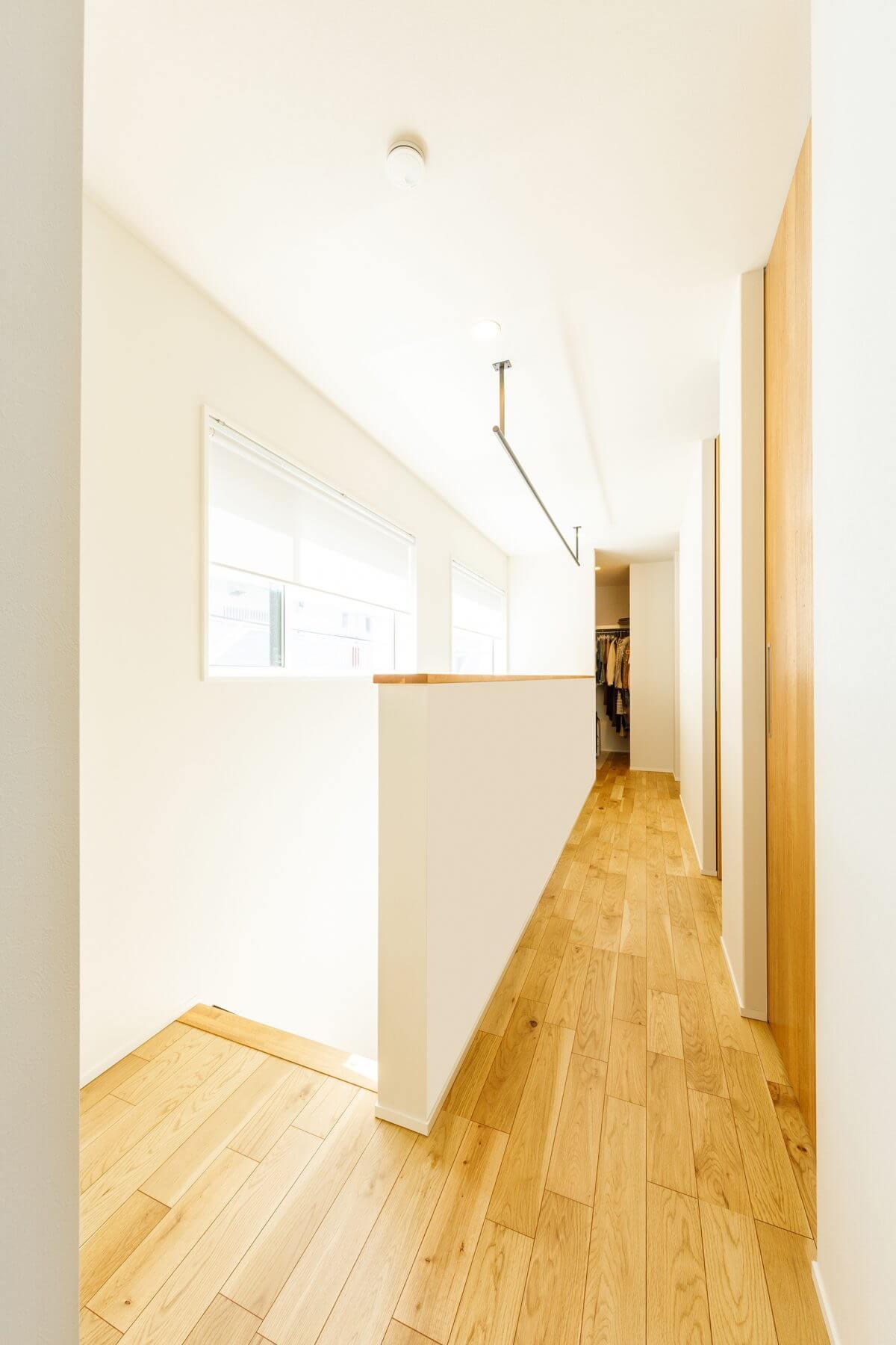 洗面室を背中に、2階の廊下を見た様子。あえてバルコニーを設けていないため、この廊下に部屋干し用のアイアン製のバーを設置しました。その奥にはWICも設けて、「洗濯→部屋干し→収納」というスムーズな家事動線を実現しました。