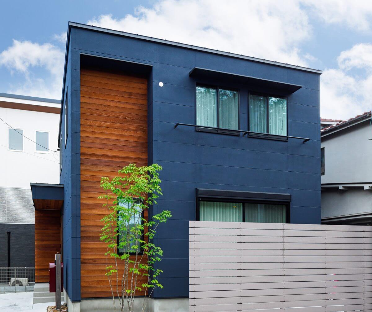 角地にあるYさんの住まいは、正面に加えて写真の南西側も印象的なデザインに設計されています。Yさんが「モダンなそば屋さん」と称する藍染のような濃紺の外壁に、板塀を思わせるアクセントウォールを組み合わせたデザイン。シンボルツリーの緑が良く映えます。
