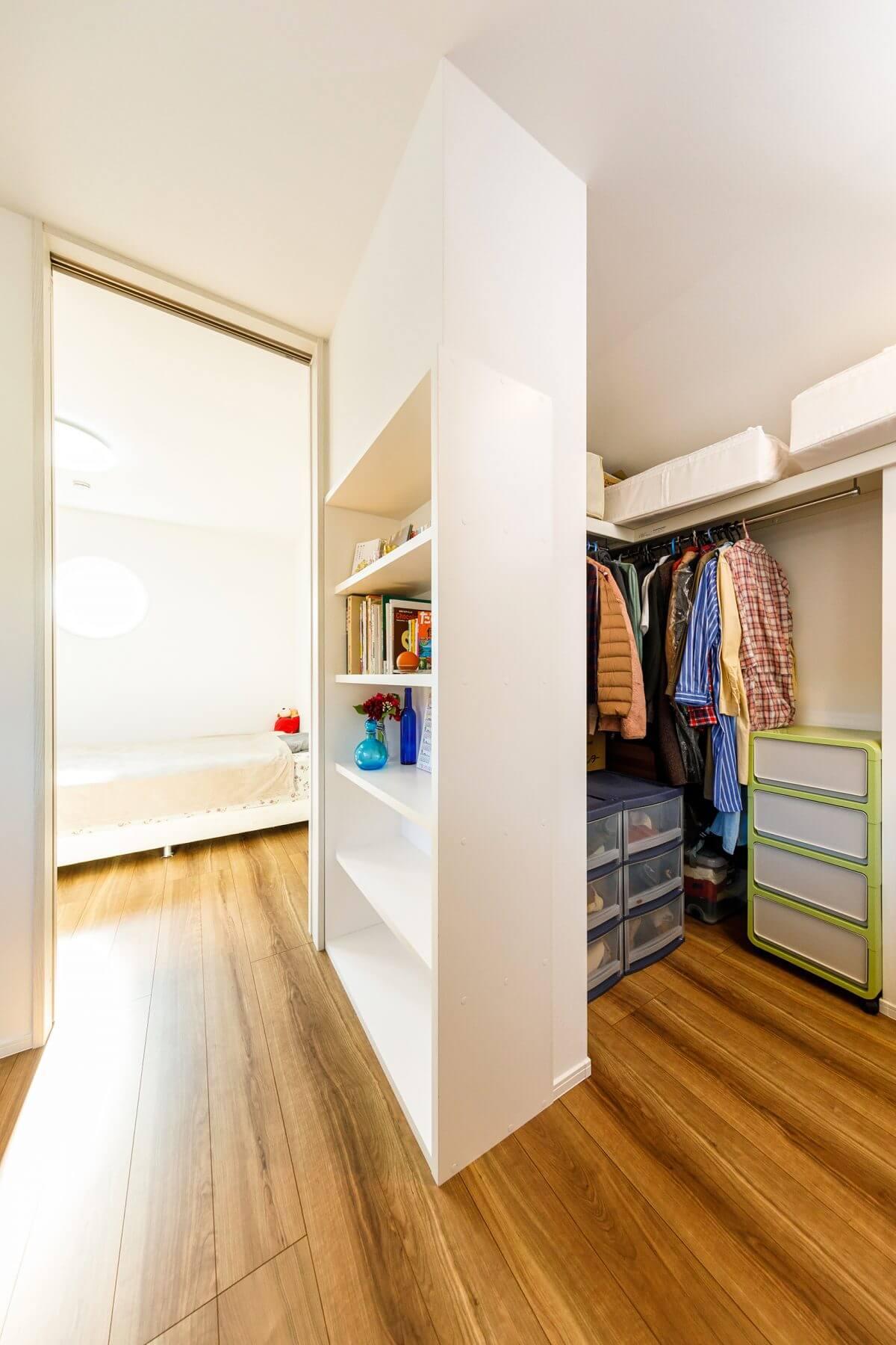 無駄な建具を使わずにオープンにした2階のファミリークローゼット。造作の収納棚で視覚的に間仕切るなど、無駄のない設計に。写真奥は主寝室です。