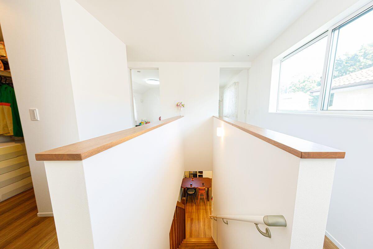 面白間取りに仕上がった2階のホール。階段を上がると奥の個室へとつながる2つの廊下が出現します。向かって左側はファミリークロゼットに、右側の廊下部分は、天井に物干し竿を取り付けることができ、室内干しのスペースとしても機能。干した衣類を取り込み、クローゼットへしまうまでの動線を効率化しました。