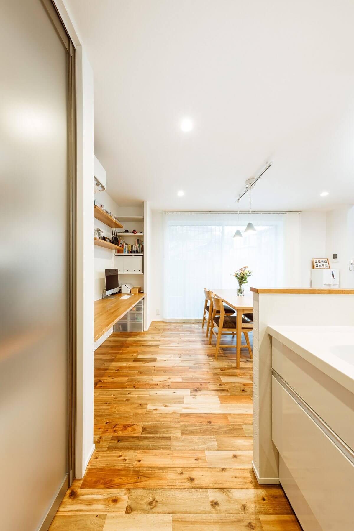 キッチン設備は使いやすさ重視で、シンプルな白に統一。背面の造作収納はシースルータイプの建具を使い、キッチン家電や食材を置いた中の様子がほどよく見えるようにしました。ダイニングテーブルの隣に見えるのが、テレワークもできる多目的カウンター。