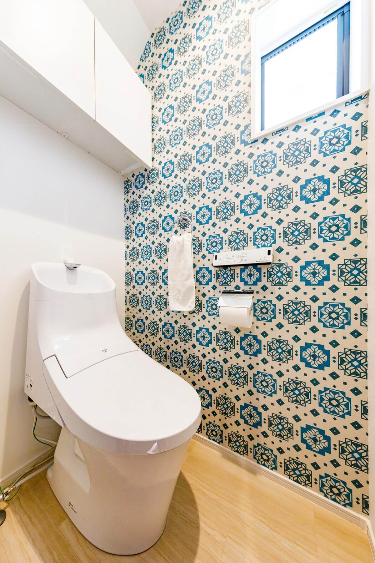 目の覚めるターコイズブルーの幾何学模様の壁紙をあしらったトイレ。限られた空間を遊び心を交えてセンス良くコーディネートしました。