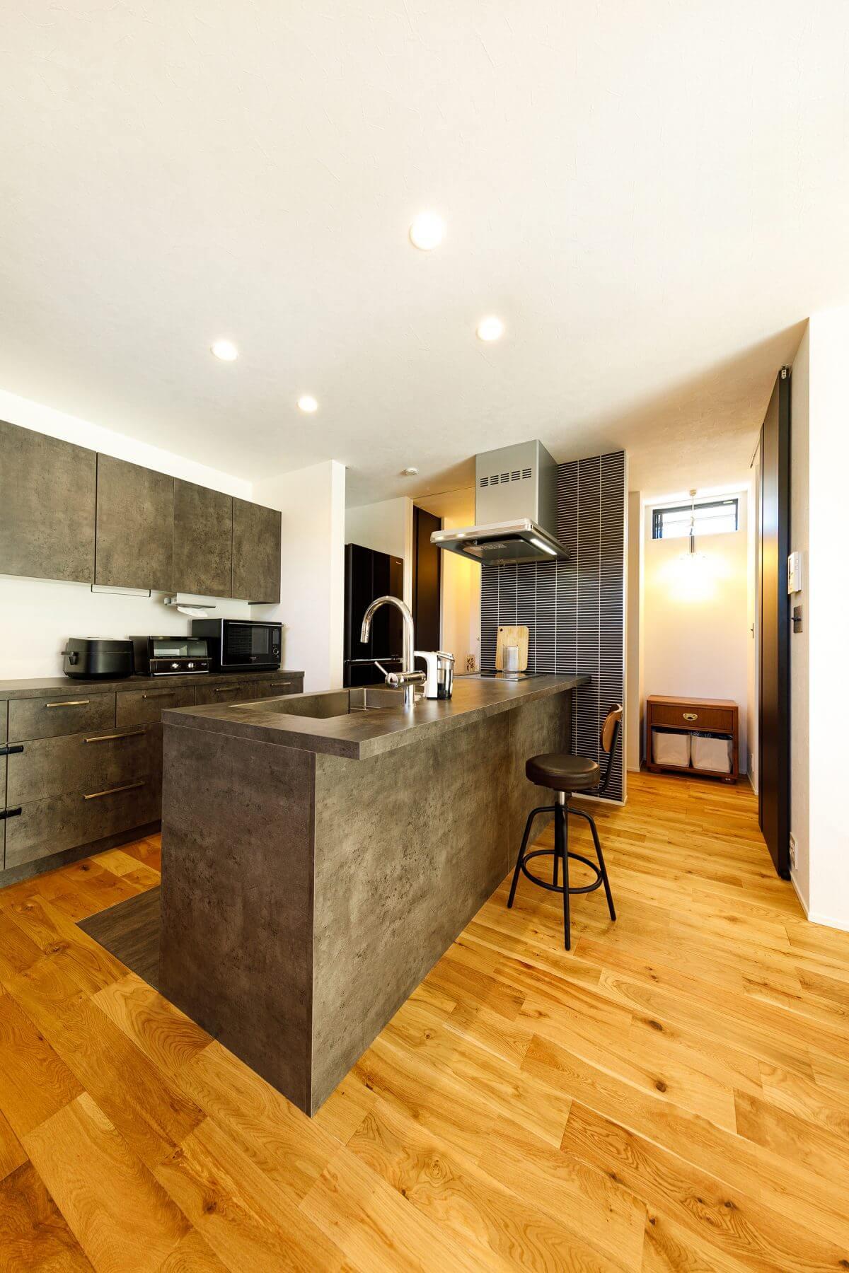 キッチン設備は土間の質感に合わせてデザインしたグラフテクト製。背面のカップボードもセットでコーディネートしました。床のオークの無垢材とも良くマッチし、カフェのような雰囲気も演出します。