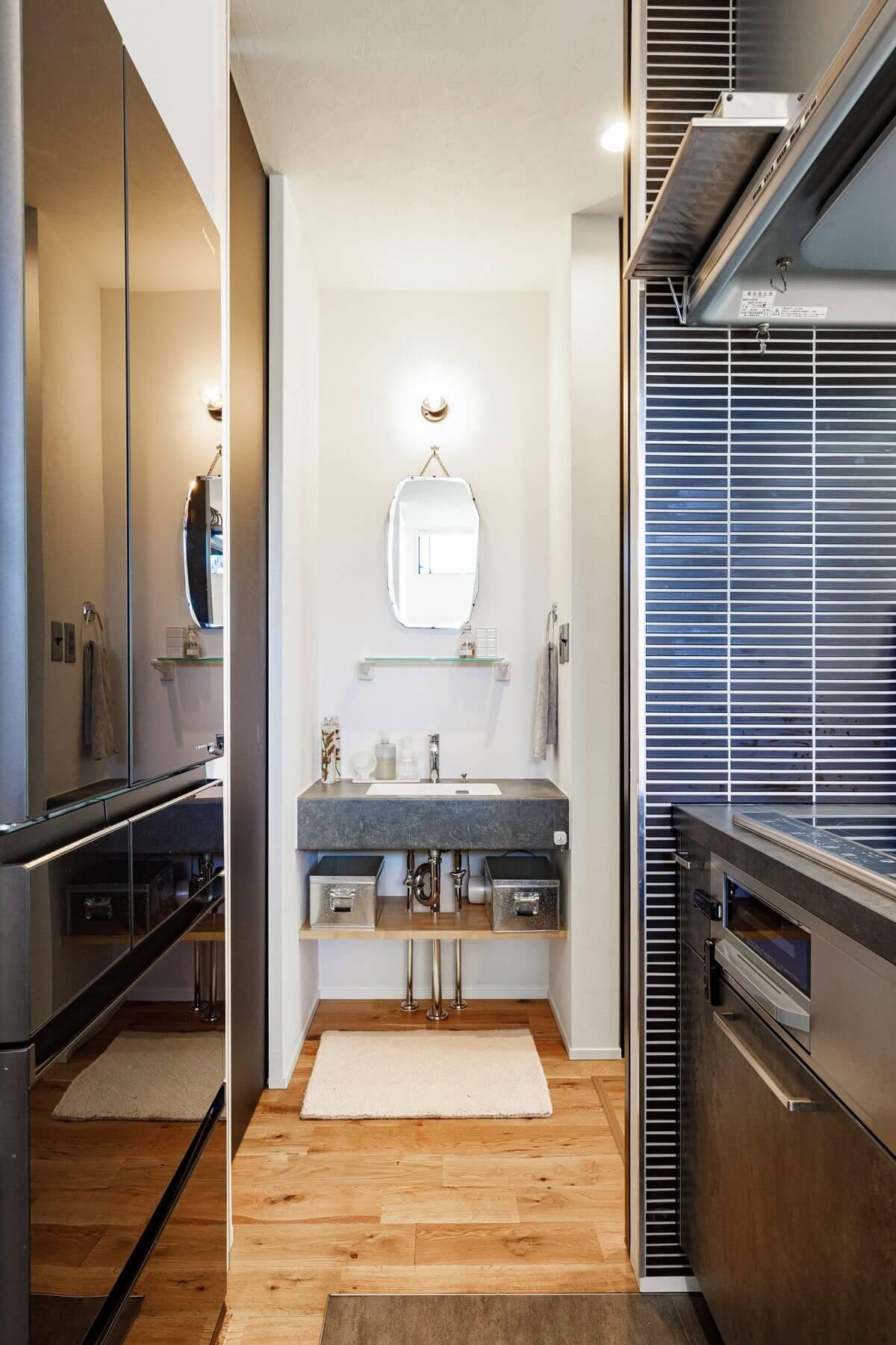 キッチンの奥には引き戸があり、そこを開けると手洗いコーナー、水まわりへと繋がっています。キッチンを起点にグルグルと回れる、回遊式の家事動線を採用しています。