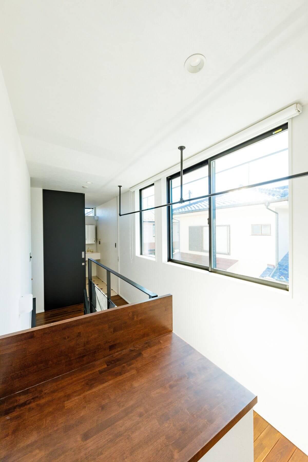 南面に位置する階段吹き抜けの2階天井には、物干し用のポールを設置。バルコニーは設けていないため、部屋干しはここで行っているそうです。「陽当たりが良いので、洗濯物はすぐに乾きます」と奥様はニッコリ。手前は、洗濯物を畳むスペース(専用台)。