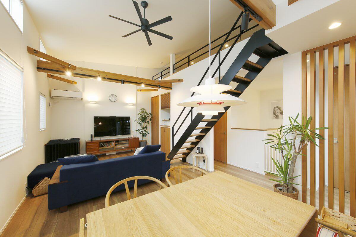 A邸のメインスペースである2階のLDK。勾配天井を見せる吹き抜けの空間としたことで、開放感抜群の住空間に。ロフトへ続くアイアン製の黒い階段がメリハリある空間を創出しています。