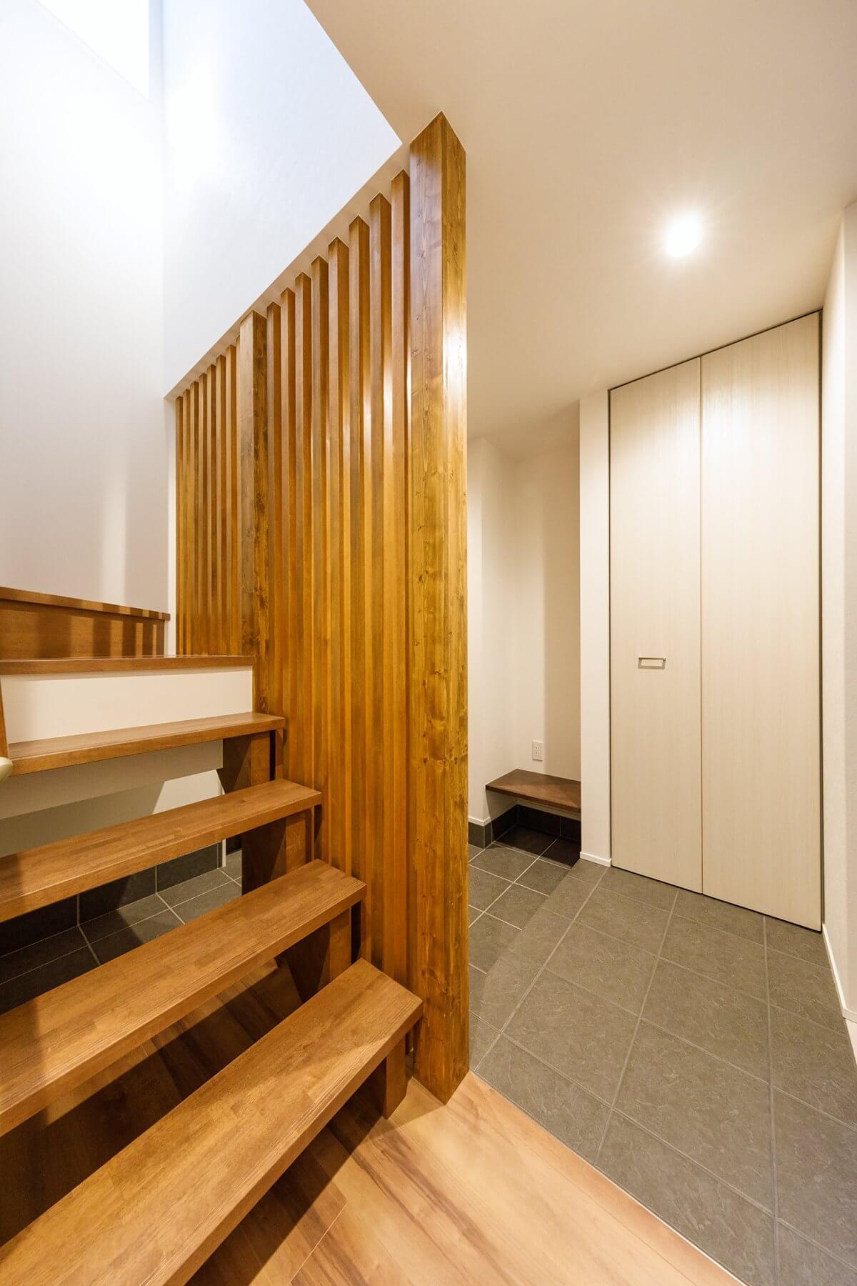 一部タイル貼りにした、土間のような雰囲気がある玄関。階段下をあえてふさがずオープンにしたり、壁ではなく光が抜ける縦格子を採用するなど、限られた空間でも視線が抜けるように工夫。面積以上に広く感じることができるように設計しました。