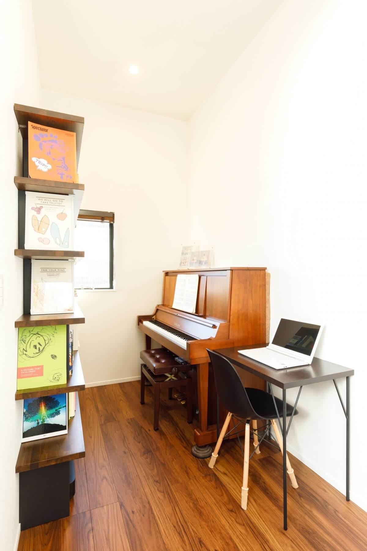 1階から階段を上がった場所にあるのが、写真のピアノスペース。造作の本棚やPCコーナーも配置し、多目的に利用されています。